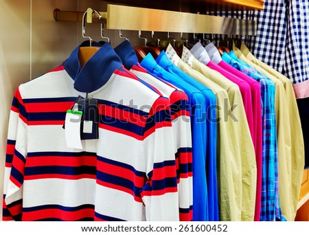 A row of colorful row t-shirts hanging on hangers - stock photo