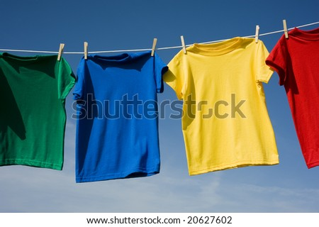 A row of colorful row t-shirts hanging on hangers on a blue sky background