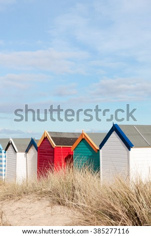 A row of colourful beach huts in Southwold, UK - stock photo