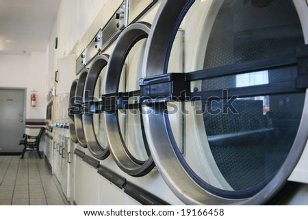 a row of commercial laundry drying machines at a laundromat