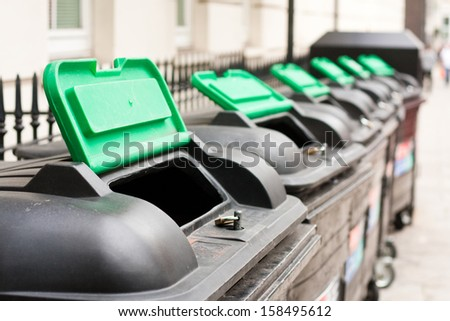 A row of commercial wheelie bins with their lids open - stock photo