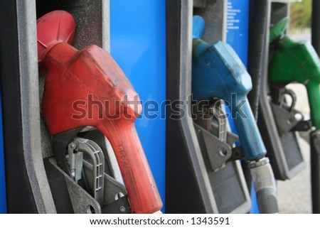 A row of 3 different gas pumps with focus on the first one. - stock photo