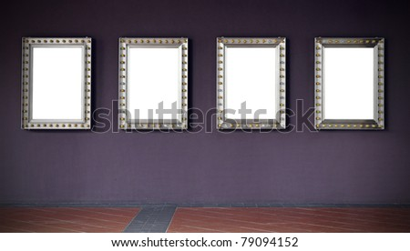 A row of four picture frames with incandescent light bulb surrounding its border hanging on a purple wall, with copy space for text and images along a rustic clay tile pavement in an exhibition hall. - stock photo