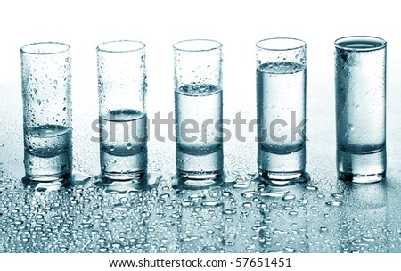 A row of glasses for vodka - stock photo