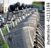 A row of green rental bikes with plastic baskets - stock photo