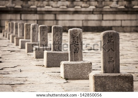 A row of Korean rank stones, or pumgyeseoks, in the courtyard of the royal Gyeongbokgung Palace. Before an audience with the king, nobles would line up according to the ranks shown on the pillars. - stock photo