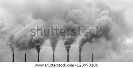 A row of metal chimney spewing heavy smoke polluting the sky. - stock photo