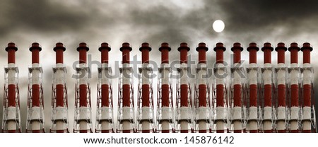 A row of metal industrial chimney against a polluted hazy sky with a sun.  - stock photo