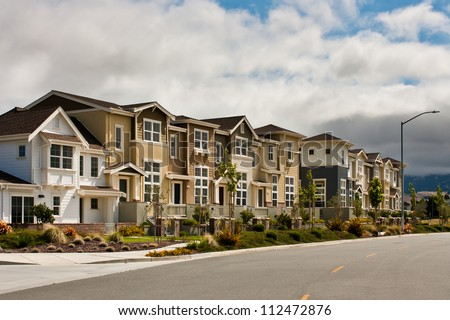A row of new townhouses / condominiums along a city street. - stock photo