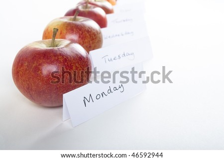 A row of organic red apples shot obliquely from side, with a folded sign in front of each stating a day of the week.  White background with natural shadows..