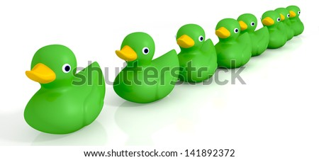 A row of organized and ready yellow rubber bath duck toys facing uneven directions on an isolated background - stock photo