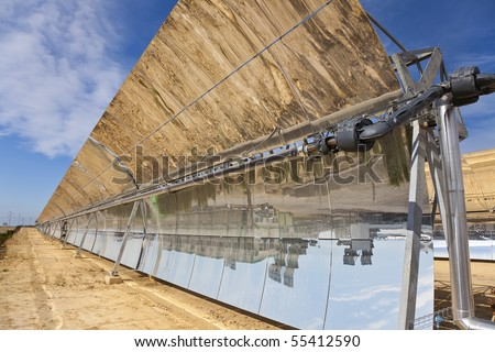 A row of parabolic trough solar mirror panels harnessing the sun's rays to provide renewable alternative green energy - stock photo