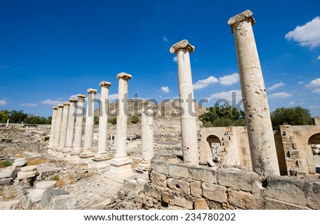 A row of pillars between the ruins of the roman period in Beit She'An in Galilee in Israel - stock photo