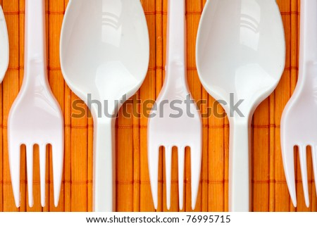 a row of plastic silverware spoons and forks