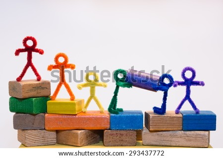A row of rainbow pipe-cleaner people across children's building blocks with two helping each other to move a block. Wonderful photo for multicultural, international ideas and concepts. - stock photo