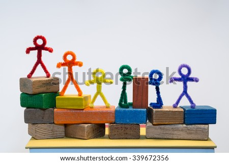A row of rainbow pipe-cleaner people across children's building blocks with two sharing or helping each other with a block. Wonderful photo for multicultural, international ideas and concepts. - stock photo