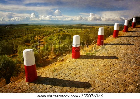 A row of red and white roadside pillars in a rural landscape - stock photo
