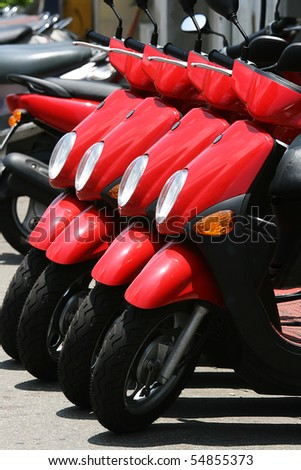 A row of red scooters.  These scooters are for hire at a holiday destination.
