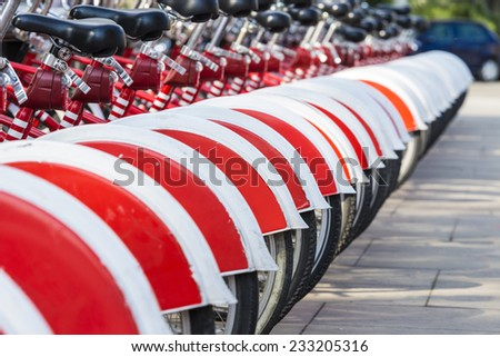A row of rental bikes in their docking stands in downtown Barcelona, Catalonia, Spain - stock photo