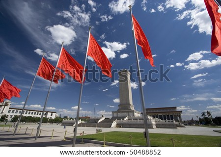A row of revolutionary flags on Beijing's Tian-An-Men square, China, with the revolution memorial in the background