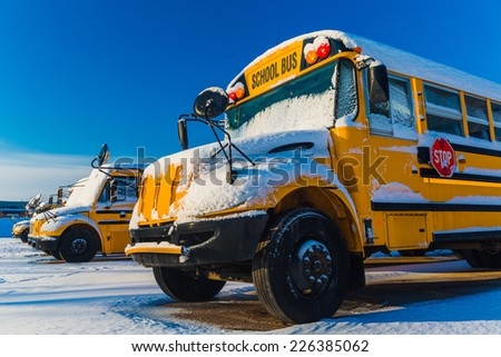 A row of school buses after a snowfall - stock photo