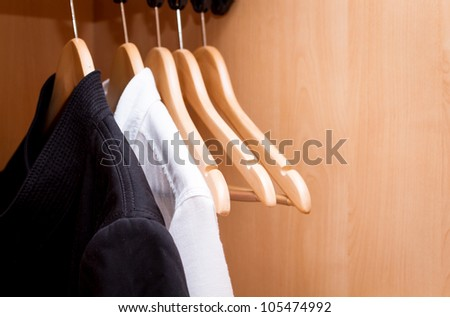 A row of shirts hanging in the closet. - stock photo
