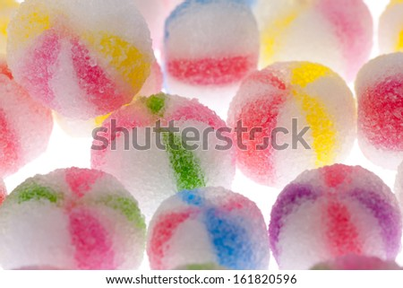 A row of striped candy balls laying together. - stock photo