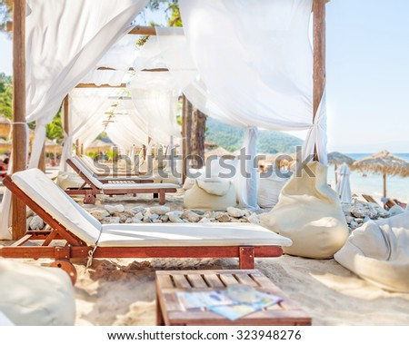 A row of Sunbed umbrellas and sunbed on the beach - stock photo