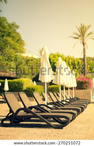 A row of sunbeds near a swimming pool at a tropical resort. Shallow DOF, focus on the nearest sunbed, lightly toned - stock photo