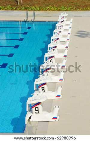 A Row Of Swimming Pool Starting Blocks At The pool Edge. - stock photo