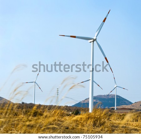 A row of turbines of windmills at Jeju Island of South Korea - stock photo