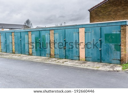 A row of untidy garages in the UK for rent via a local council - stock photo