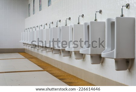 A row of urinals in tiled wall in a public restroom.  - stock photo