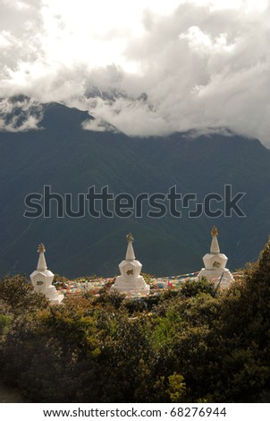 A row of white and Gold Tibetan Stupas with mountainous backdrop in China - stock photo