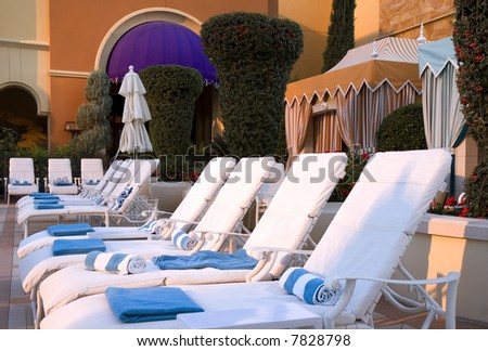 A row of white chaise lounges outside a colorful cabana - stock photo