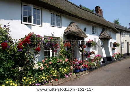A row of whitewashed thatched cottages in a Devon village - stock photo