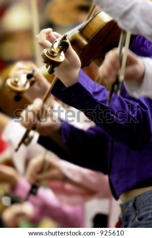 A row of young people playing fiddles or violins (shallow focus). - stock photo