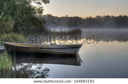 A rowboat by a pier on a calm Swedish lake with mist drifting across. It is early morning and everything is quiet. - stock photo