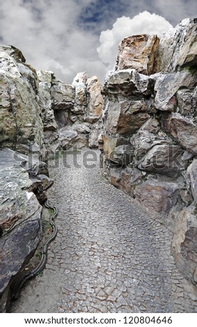 A rubble road through a rocky chasm against a dramatic blue cloudy sky. - stock photo