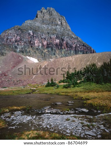 A Rugged Ice Sculpted Peak Overlooking Hidden Lake At Glacier National Park, Montana, USA - stock photo