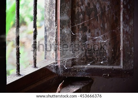A ruined, haunted house. Window of an old house with rusted iron bars and cobweb. Ghost house. - stock photo