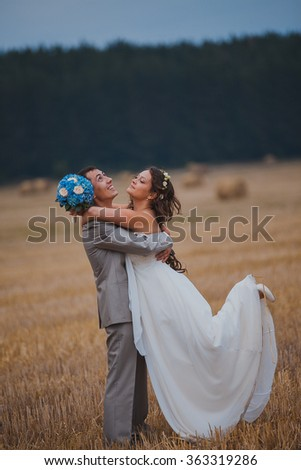 a runaway bride and groom dancing on a field - stock photo