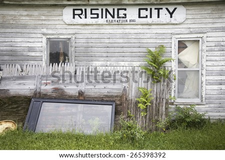 A rundown house with a sign on it's side that reads Rising City, Nebraska - stock photo