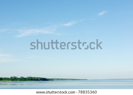 A rural blue lake and a green forest - stock photo