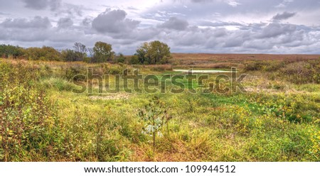 A rural landscape of prairie grassland extending as far as the eye can see, meeting the horizon and approaching storm clouds. - stock photo