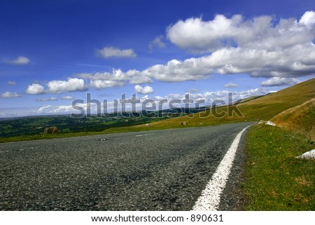 A rural mountain road, with fields, trees and hills in the distance with a blue sky and  clouds. Set in the Brecon Beacons National Park, Wales, UK.