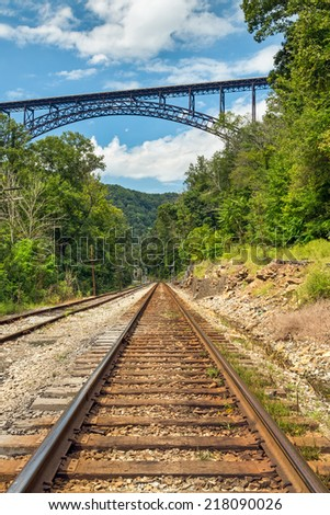 A rural railroad track points to one of the world's largest and highest bridges, The New River Gorge Bridge, near Fayetteville, West Virginia. - stock photo