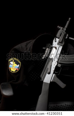 A Russian Federation police jacket and assault rifle resting on an office chair.