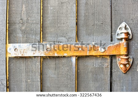 A rusted metal hinge on a wooden gate - stock photo