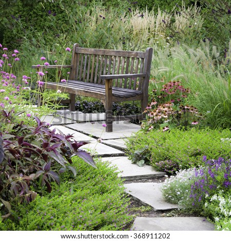 A rustic bench invites visitors to rest and enjoy the wonderful garden architecture of Cantigny Park in Wheaton, Illinois. - stock photo